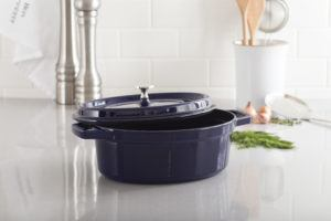 dark blue cast iron oval staub cocotte with lid ajar