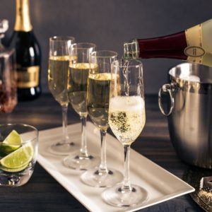 champagne flutes with champagne on a white platter