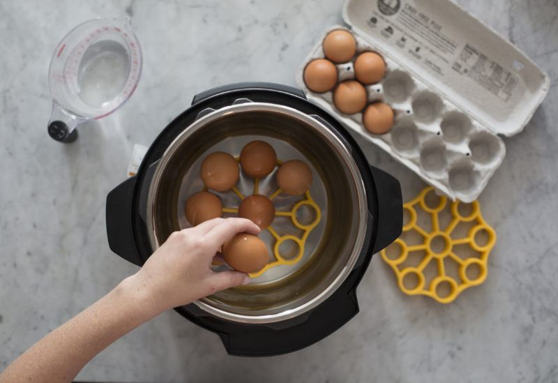pressure cooker egg rack inside a pressure cooker with eggs on it and water covering eggs