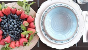 blue speckled melamine bowl stacked on top of plates and a charger