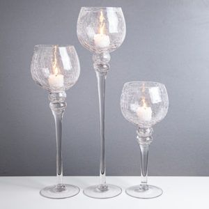 3 glass stemmed candleholders with a candle in each