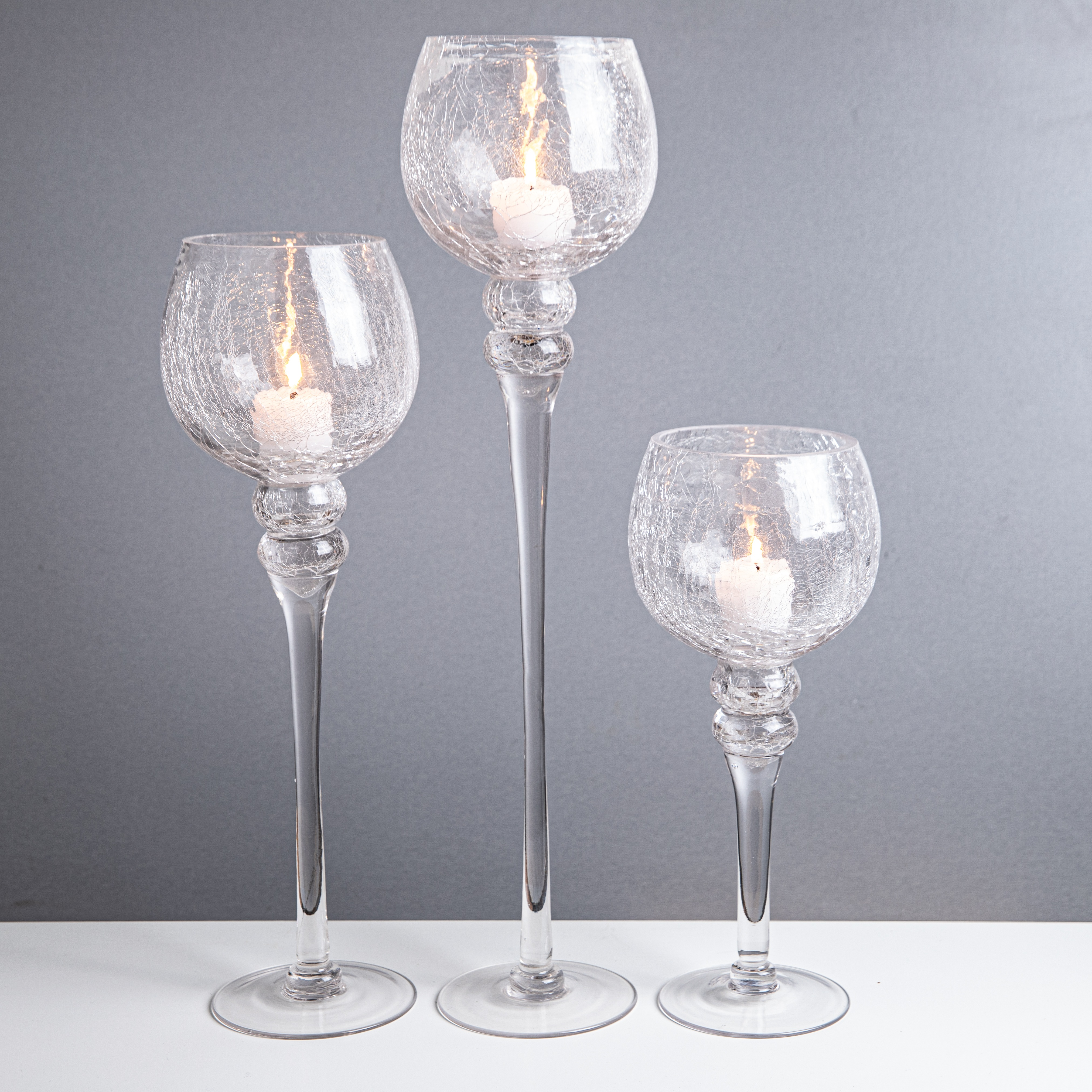 3 glass stemmed candleholders with a candle in each - weddings centrepiece
