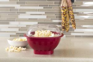 popcorn in a red bowl with a clear dome lid