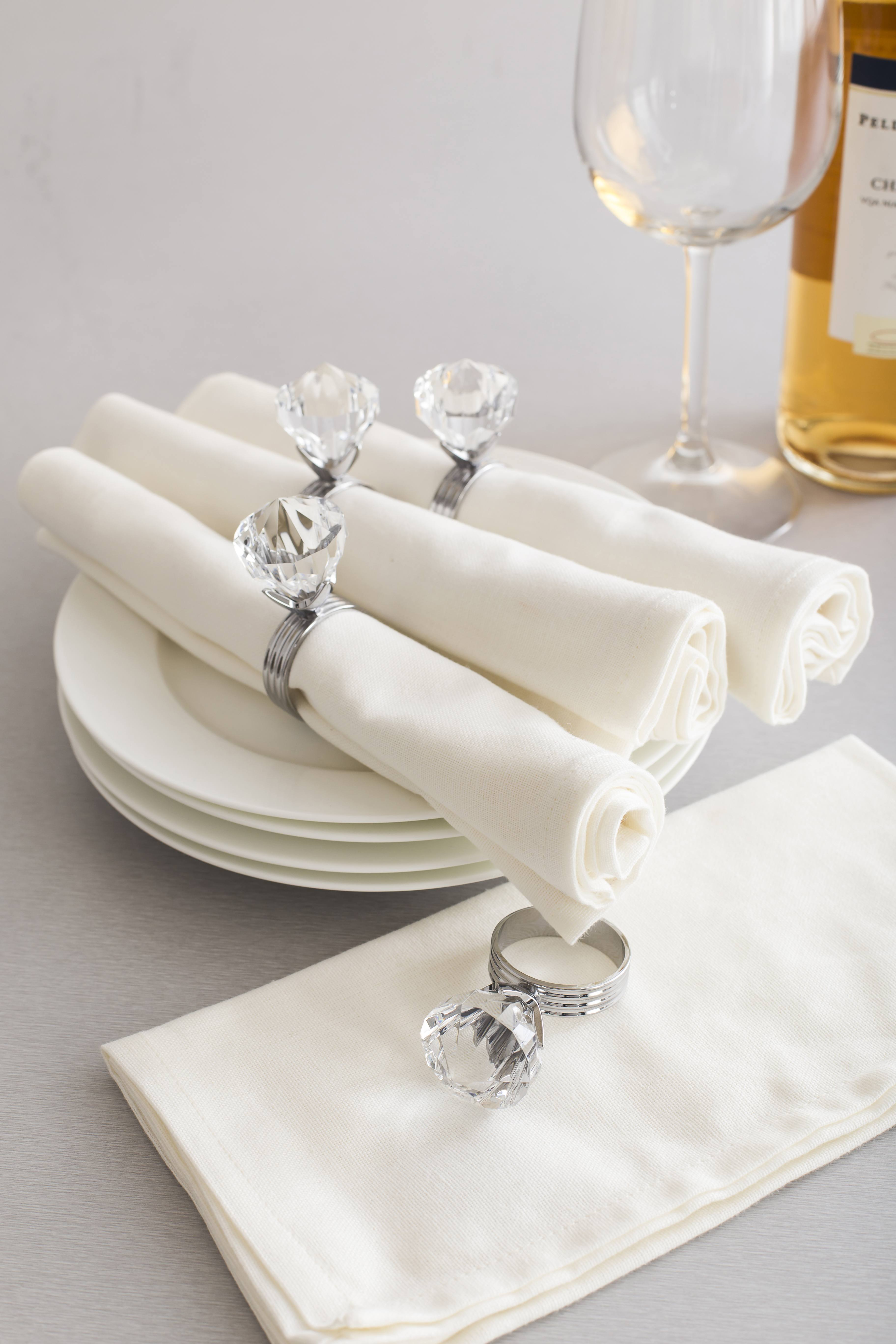 white napkins rolled and secured with a napkin ring with an acrylic diamond on top - best for weddings