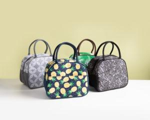 4 duffle lunch bags, one with a tropical leaf print, one with a pinapple print, one with a pebble-like print, and one with a paragon print