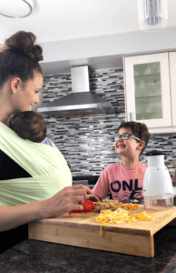 mom and child smiling at each other while prepping veggies with a food chopper