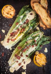 grilled romaine leaves topped with caesar dressing and pancetta with grilled lemons and grilled baguette slices in the background