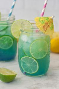 green-blue adult punch in a glass mason jar with sliced limes and a decorative umbrella and pink stripped straw