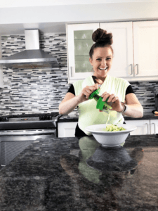 woman spiralizing vegetables into a bowl