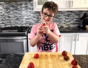 boy using strawberry huller