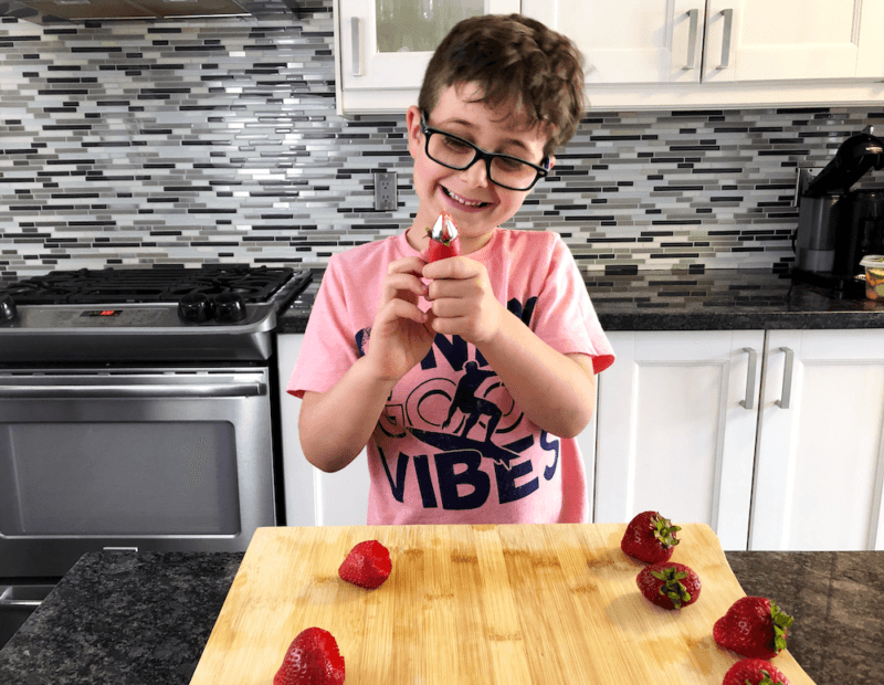 boy using strawberry huller