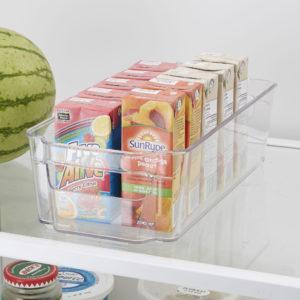 clear storage bin on a fridge shelf filled with juice boxes