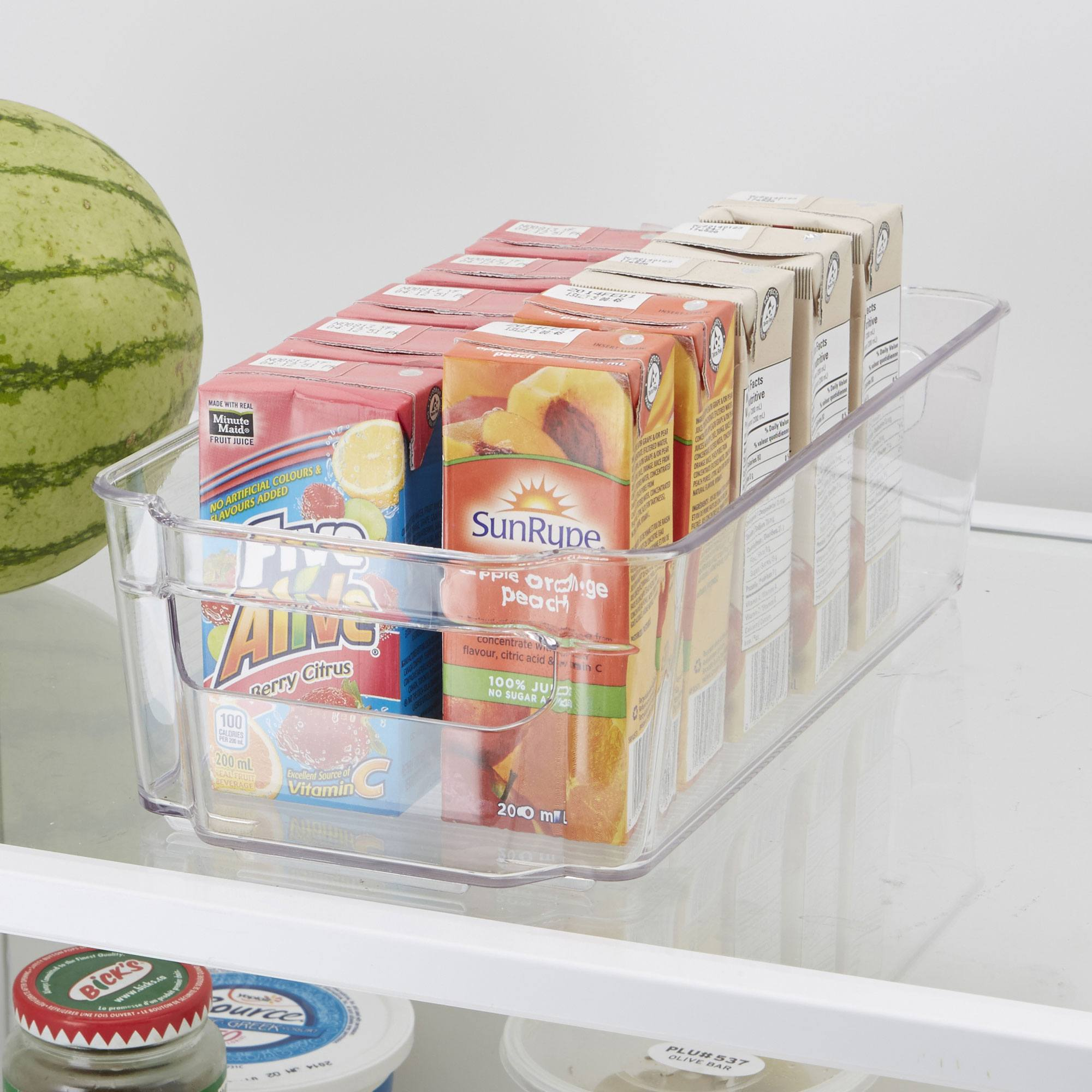 clear storage bin on a fridge shelf filled with juice boxes - snack stations