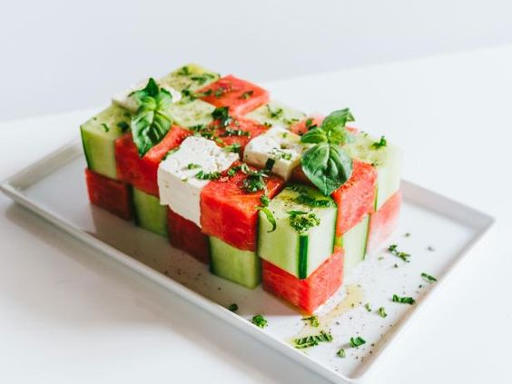 salad with cubes watermelon and cubed cucumber stacked on a plate