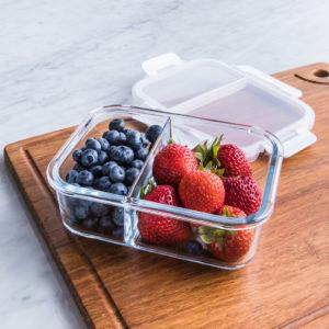 divided glass container, one side with blueberries, one side with strawberries