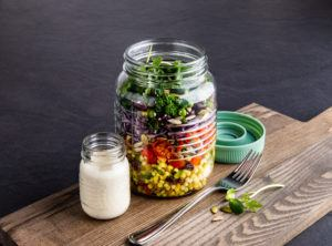 glass salad mason jar with salad inside and dressing in a mini jar on the side