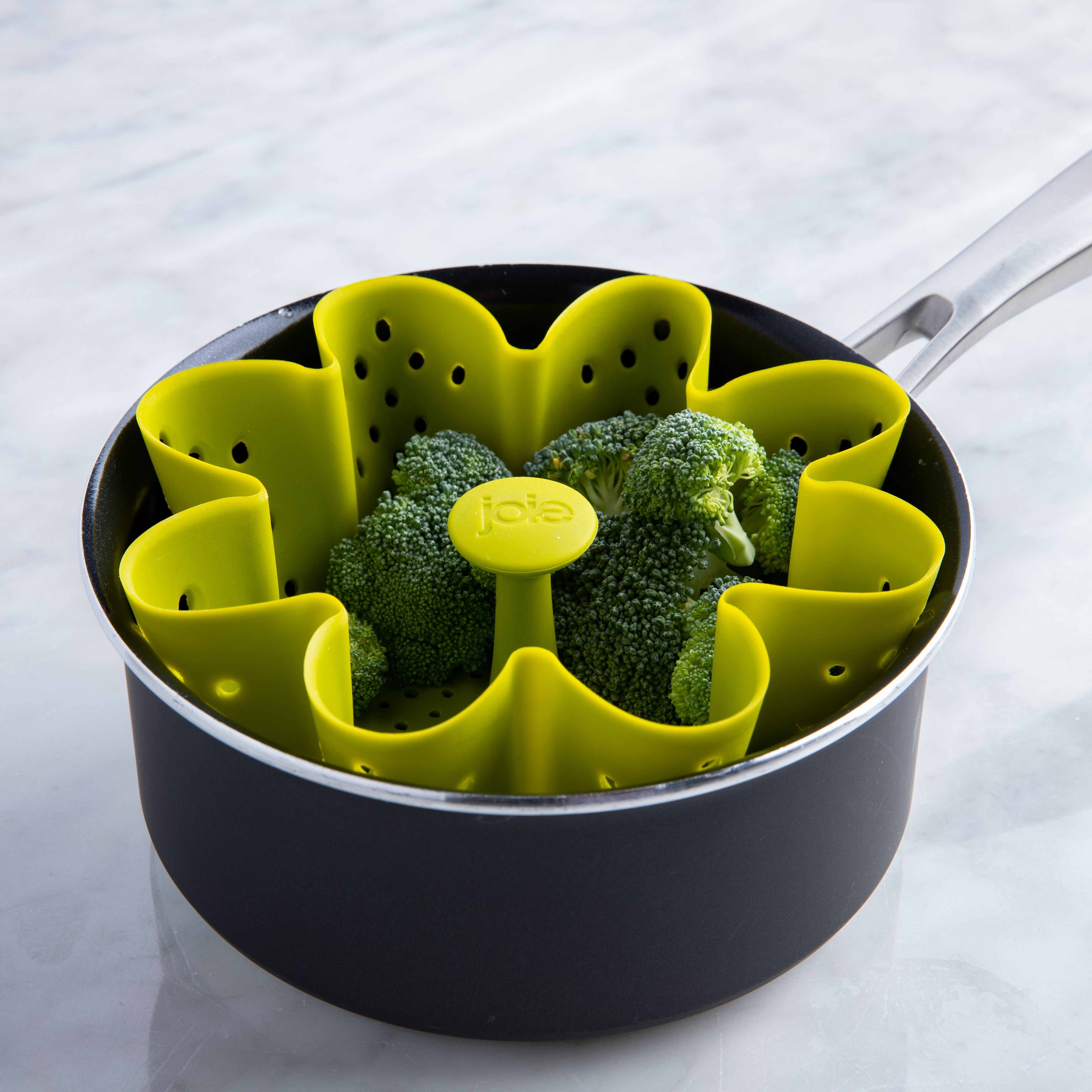 green silicone steamer filled with broccoli inside a pot