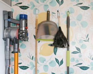 cleaning supplies hanging from hooks on a wall