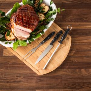 3 piece carving set on a cutting board beside a partially sliced roast
