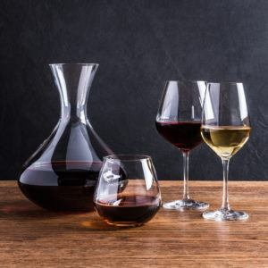 a wine decanter, stemless wine glass, red wine glass, and white wine glass filled with wine