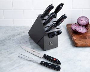 knives in a charcoal coloured knife block with a carving knife and carving fork to the side