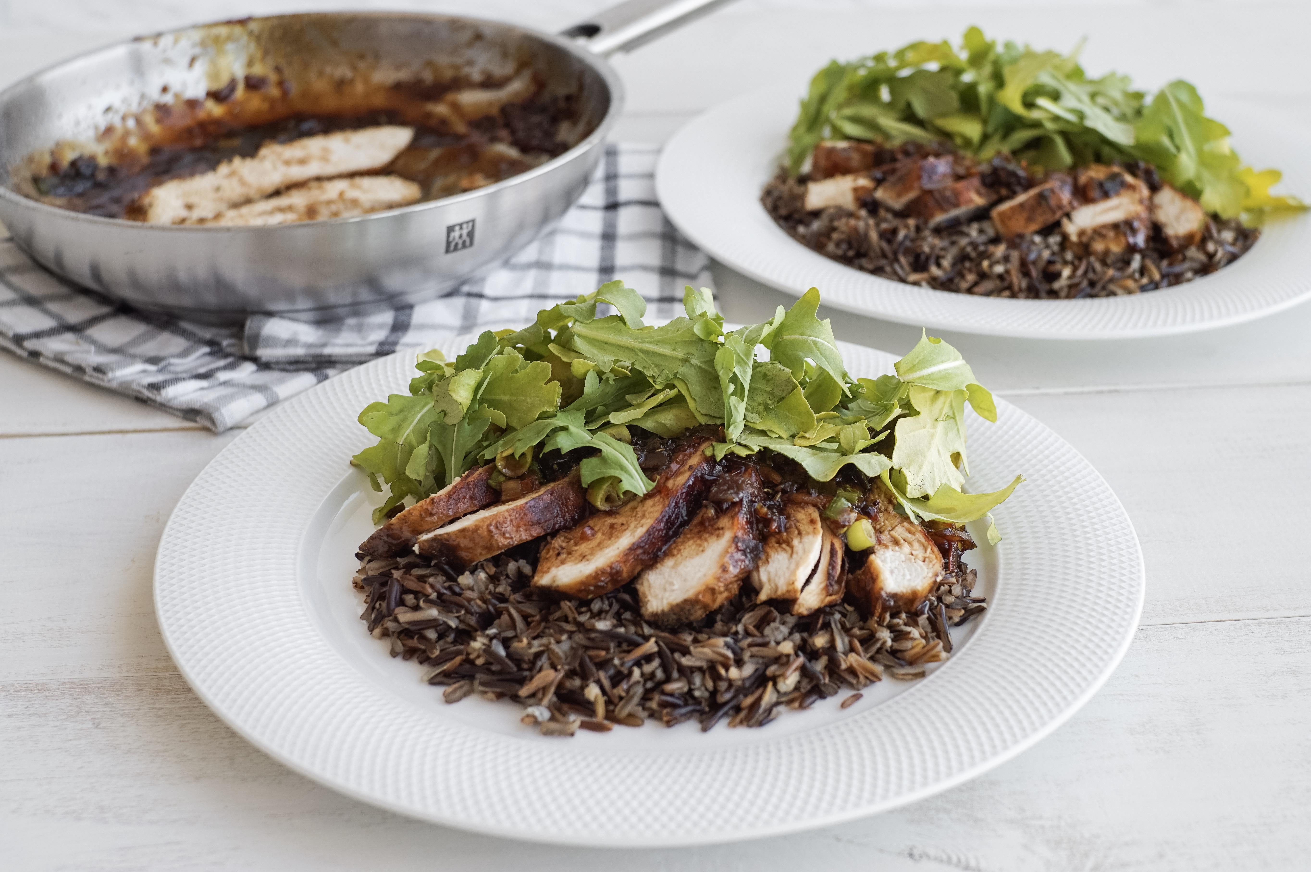 glazed balsamic chicken on a bed of rice and topped with arugula