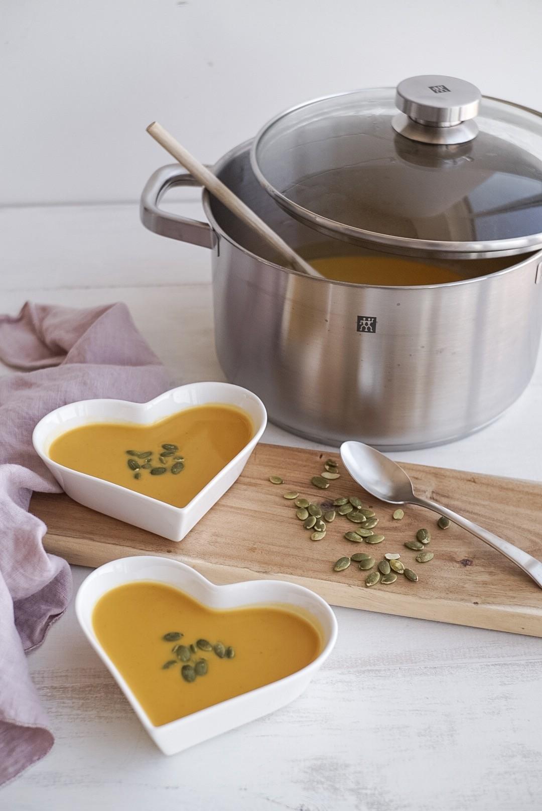 stock pot of butternut squash soup beside heart shaped bowls