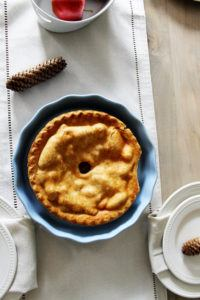 light blue pie dish with an apple pie inside