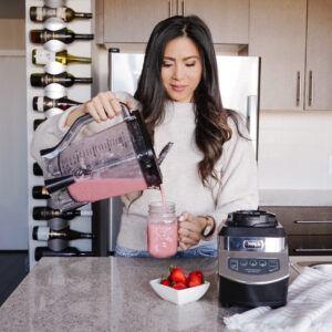 Charlene pouring strawberry smoothie into mason jar