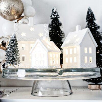 lit up christmas village displayed on cake plate