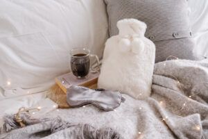 hot water bottle and faux fur eye mask draped with twinkle lights