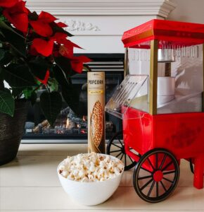 bowl of popcorn beside old fashioned popcorn machine