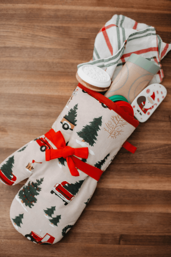 tea towel, cookie press, silicone baking mat, & spatula bundled into a Christmas themed oven mitt