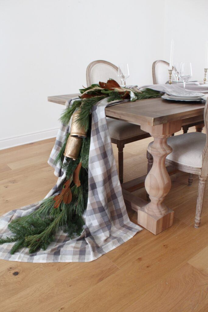 holiday tablecloth draped over table with garland closer side view