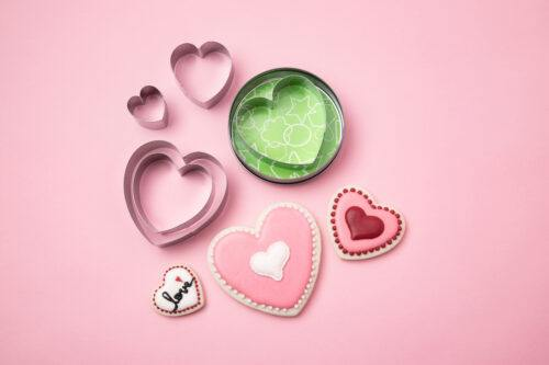 heart shaped cookie cutters and cookies with pink background